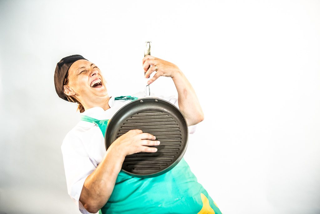 A dinner lady pretends to play the guitar using a skillet pan.
